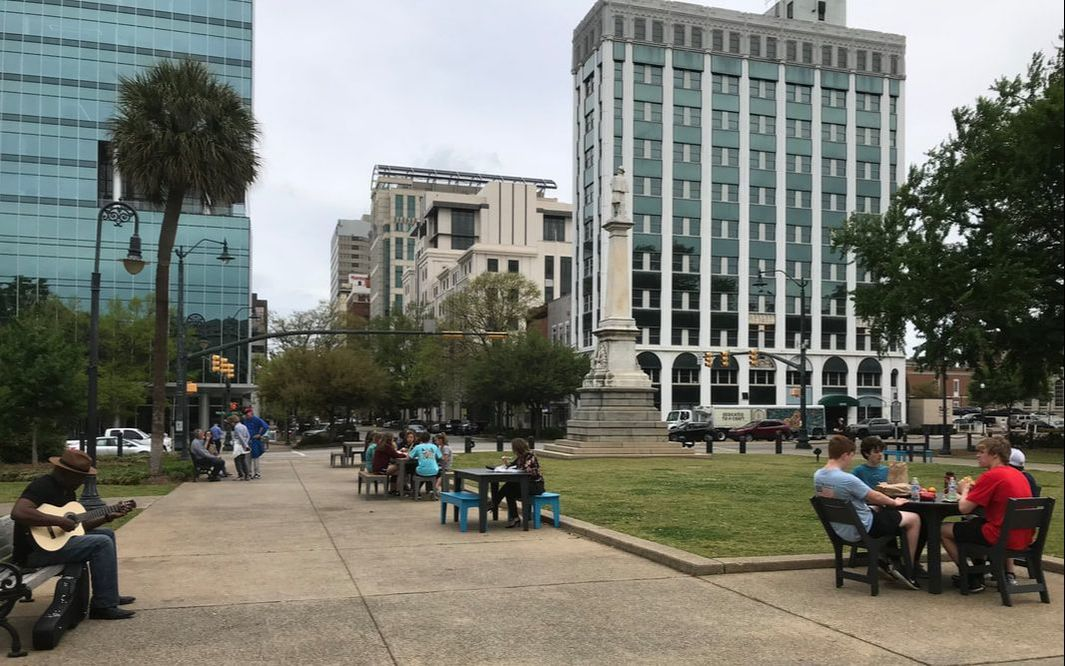 a photo of individuals enjoying the state house grounds with gervais and main streets in the background.  Folks are sitting at tables, playing a guitar, etc.